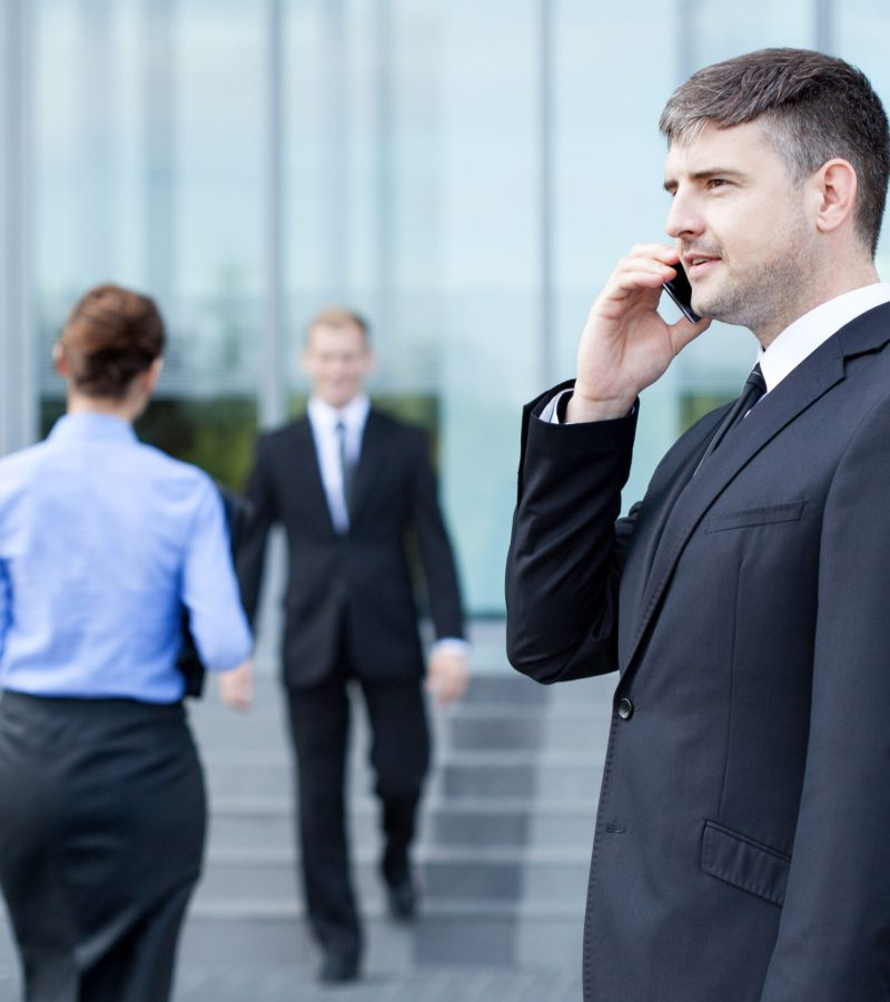 Man talking on phone in front of business centre